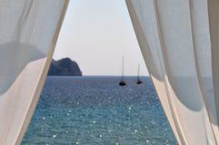 Bateaux blancs de rideaux par la mer Image libre de droits