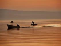 Bateaux dans la brume et le coucher du soleil Photos stock