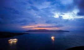 Bateaux de croisière dans le port après coucher du soleil chez Santorini Photos libres de droits