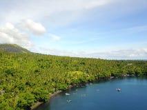 Bateaux de Fisherspar la plage et la forêt dans le détroit de Lembeh Photographie stock