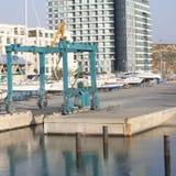 Bateaux de levage de grue au port Photo stock