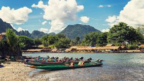 Bateaux de longue queue sur le coucher du soleil à la rivière de chanson, Vang Vieng, Laos photos stock