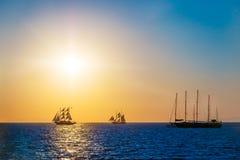 Bateaux de navigation sur la mer dans le coucher du soleil Photographie stock libre de droits