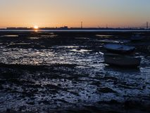 Bateaux de pêche échoués dans le sable humide au coucher du soleil Photos libres de droits