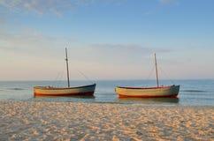 Bateaux de pêche amarrés près du rivage au fond de coucher du soleil photo stock