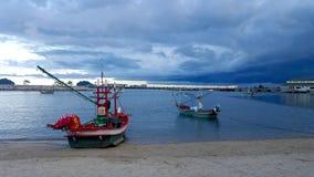 Bateaux de pêche ancrés par la plage tandis qu'une tempête s'approche, Prachuap Khiri Khan, Thaïlande Photo stock