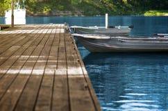 Bateaux de pêche en aluminium au dock en bois Photos stock