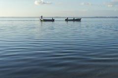 Bateaux de pêche qui croisent à l'aube avec la mer calme photo stock