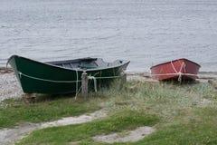 Bateaux de pêche rouges et verts attachés avec la corde Photo stock