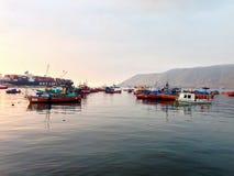 Bateaux de pêche sur l'eau calme au coucher du soleil Photos stock