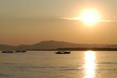 Bateaux de pêche sur le fleuve d'Irawaddy au coucher du soleil Photo libre de droits