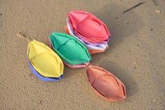 Bateaux de papier coloré sur le sable Photographie stock libre de droits