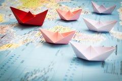 Bateaux de papier suivant un bateau rouge de chef Photographie stock