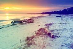 Bateaux de pêche ancrés à la plage sablonneuse de la mer baltique, Lettonie Photographie stock libre de droits