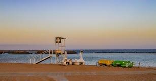 Bateaux de station et de pédale de garde-côte sur la plage avec le rouge images stock