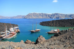 Bateaux de touristes d'excursion au petit port sur le volcan de Santorini Photographie stock libre de droits