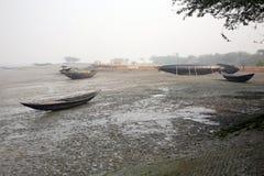 Bateaux des pêcheurs échoués dans la boue à marée basse sur la ville de mise en boîte proche de Malte de rivière, Inde Images stock