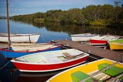 Bateaux en bois de couleur avec des palettes dans un lac Images libres de droits