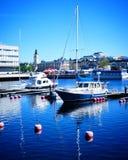 Bateaux en eau bleue et ciel de port Photos stock