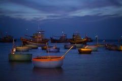 Bateaux et paniers de pêche au coucher du soleil Image stock