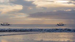 Bateaux flottant au coucher du soleil Image libre de droits