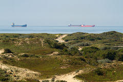 Bateaux industriels sur la mer avec des dunes Photographie stock libre de droits