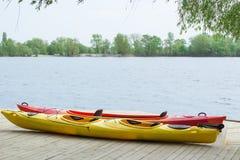 Bateaux Kayaking sur la plate-forme en bois à la station près de la rivière Image stock