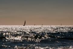 Bateaux naviguant sur la mer de la Sardaigne éclairée à contre-jour image stock