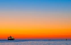 Bateaux par la mer au coucher du soleil Photographie stock libre de droits