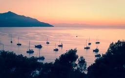 Bateaux privés et petits yachts ancrés dans une baie tranquille dans il Photos stock