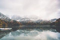 Bateaux sur l'eau de lac et la forêt conifére d'automne Photographie stock libre de droits