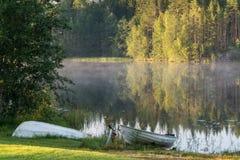 Bateaux sur la côte du lac finlandais au début de la matinée Photos libres de droits