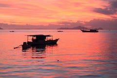 Bateaux sur la mer de coucher du soleil Photographie stock libre de droits