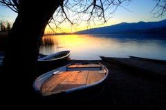 Bateaux sur le rivage du lac au coucher du soleil Photos stock