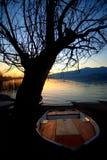 Bateaux sur le rivage du lac au coucher du soleil Photo libre de droits