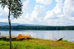 Bateaux sur le rivage du lac Forêt et ciel nuageux à l'arrière-plan Photos stock
