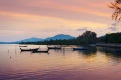 Bateaux thaïlandais traditionnels de longue queue au coucher du soleil Images stock