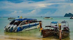 Bateaux thaïlandais traditionnels de Longtail et nouveaux bateaux de vitesse sur l'île de Phi Phi, Thaïlande Photo libre de droits