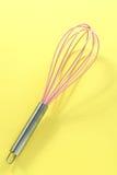 Batedor de ovos cor-de-rosa da cozinha no fundo amarelo Imagem de Stock