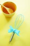 Batedor de ovos da cozinha de turquesa no fundo amarelo Fotos de Stock Royalty Free