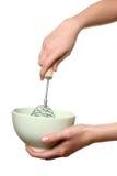 Batedor de ovos dos chicotes da mulher algo em uma bacia Fotos de Stock Royalty Free