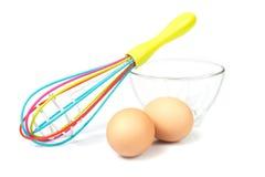 Batedor de ovos em uma bacia de vidro com os ovos na parte dianteira Imagens de Stock Royalty Free