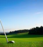 Batendo a bola de golfe com o clube para o verde Imagens de Stock Royalty Free