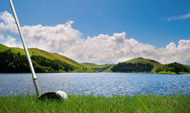 Batendo a esfera de golfe sobre o lago Fotografia de Stock