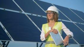 Batería al aire libre solar con un ingeniero de sexo femenino que se coloca al lado de ella y de la sonrisa metrajes