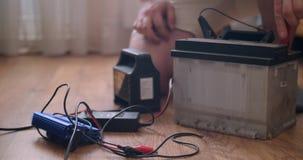 Batería de coche de la carga del hombre en casa metrajes