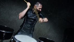 Batería que juega los tambores con agua en un estudio oscuro almacen de metraje de vídeo