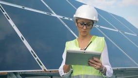 Batería solar con un ingeniero de sexo femenino que se coloca al lado de ella y que habla en un transmisor metrajes