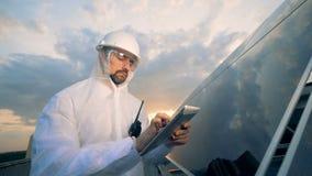 Batería solar con una situación experta masculina cerca de ella y actuando una tableta metrajes