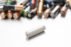 Batería universal comparada a otras baterías en un fondo blanco imágenes de archivo libres de regalías